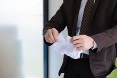 Geschäftsmann, der zerknittert wird und Vertragsvereinbarungspapier zerrissen ist, stockbild