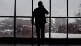 Geschäftsmann, der zum Fenster kommt und am Telefon spricht stock footage