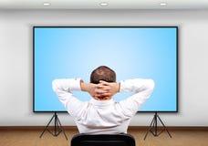 Geschäftsmann, der zum Plasmabildschirm schaut Lizenzfreie Stockfotos