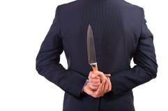 Geschäftsmann, der zurück Messer hinter seinem hält. Stockfotografie