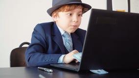 Geschäftsmann des kleinen Jungen, der an Laptop und dem Jubeln seines Erfolgs arbeitet stock video