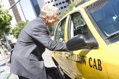 Geschäftsmann-Discussing His Taxi-Fahrpreis Stockbild