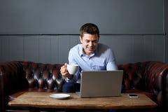 Geschäftsmann Drinking Coffee Whilst, das an Laptop im Internet arbeitet lizenzfreie stockfotos