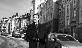 Geschäftsmann in einem Mantel, gehend um die Stadt, mit einer Tablette in den Händen, Tag, im Freien lizenzfreie stockfotos