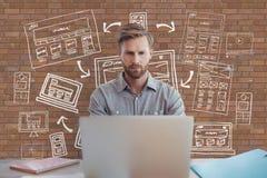 Geschäftsmann an einem Schreibtisch unter Verwendung eines Computers gegen Backsteinmauer mit Grafiken lizenzfreie abbildung