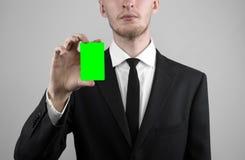 Geschäftsmann in einem schwarzen Anzug und in einer Abendgarderobe, die eine Karte, eine Hand hält eine Karte, Green Card hält, K Lizenzfreie Stockbilder