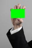 Geschäftsmann in einem schwarzen Anzug und in einer Abendgarderobe, die eine Karte, eine Hand hält eine Karte, Green Card hält, K Lizenzfreie Stockfotografie
