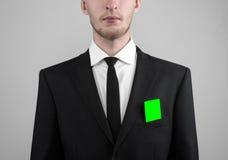 Geschäftsmann in einem schwarzen Anzug und in einer Abendgarderobe, die eine Karte, eine Hand hält eine Karte, Green Card hält, K Stockbild
