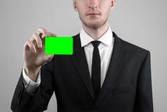 Geschäftsmann in einem schwarzen Anzug und in einer Abendgarderobe, die eine Karte, eine Hand hält eine Karte, Green Card hält, K Lizenzfreie Stockfotos