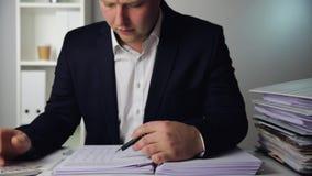 Geschäftsmann in einer dunkelblauen Klage, die Absatzerfolge berechnet Finanzbilanzauffassung