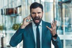 Geschäftsmann in einer fromal Klage in einer wütenden Nahaufnahme des Geschäftszentrum-Telefonanrufs lizenzfreies stockbild