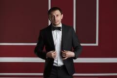 Geschäftsmann in einer Klage auf einer roten Wand Stockfoto
