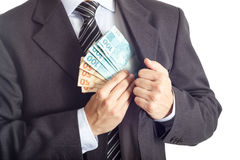 Geschäftsmann in einer Klage, die Geld in seine Tasche einsetzt Lizenzfreie Stockfotografie