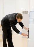 Geschäftsmann erhält Wasser vom Wasserkühler stockbild