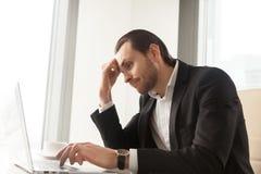 Geschäftsmann ermüdet von der Routinearbeit über Laptop stockbilder