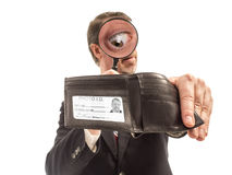 Geschäftsmann Explores Depths seiner Geldbörse mit Lupe Stockfoto