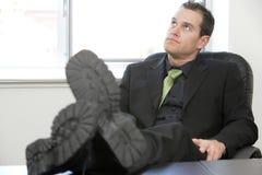 Geschäftsmann-Füße auf dem entspannenden Schreibtisch Stockfotografie