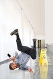 Geschäftsmann Falling auf nassem Boden Stockbild