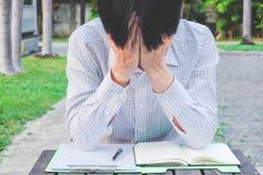 Geschäftsmann frustriert und beschämt mit den Händen auf Gesicht am Park, einsame, traurige, negative Gefühle stockfotos