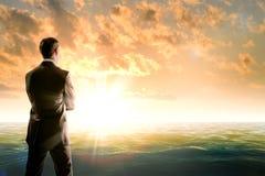 Geschäftsmann gegen Meer im Morgenlicht lizenzfreies stockfoto