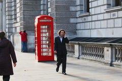 Geschäftsmann geht hinter alte rote Telefonzelle in London bei der Unterhaltung am Handy Lizenzfreies Stockfoto