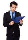 Geschäftsmann gelesen auf Klemmbrett lizenzfreies stockfoto