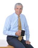 Geschäftsmann gesetzt auf dem Rand seines Schreibtisches lizenzfreies stockbild