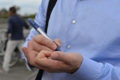 Geschäftsmann, gestoppt auf der Straße, um eine große neue Geschäftsidee auf seine Hand zu schreiben Stockfotografie