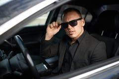Geschäftsmann gestopptes Auto und justiert Gläser Stockfotografie