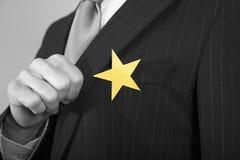 Geschäftsmann With Gold Star auf Klage stockbild