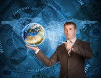 Geschäftsmann-Griff Erde Weltkarte und Geld an Stockbilder