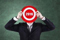Geschäftsmann hält Dartscheibe mit Nr. 2016 Stockbild