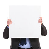 Geschäftsmann hält eine Platte vor seinem Gesicht Lizenzfreie Stockbilder