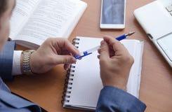 Geschäftsmann hält einen Stift in seinen Händen und wird in ein Notizbuch schreiben Lizenzfreies Stockfoto