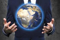Geschäftsmann hält Erde in einer Hand Stockbild