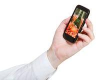 Geschäftsmann hält Mobiltelefon mit Weihnachtsstillleben Stockbilder
