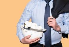 Geschäftsmann hält Schutzhelm mit Eiern stockfoto