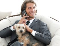 Geschäftsmann hält sein Haustier und spricht auf dem Smartphone beim Sitzen in einem bequemen Stuhl stockbild