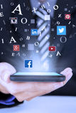 Geschäftsmann hält Smartphone mit Social Media-Symbolen Lizenzfreie Stockfotos