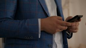 Geschäftsmann hält Telefon bei zuhause stehen stock footage