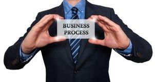 Geschäftsmann hält weiße Karte mit dem Geschäftsprozesszeichen, weiß- Stockbilder