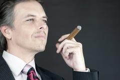 Geschäftsmann hält Zigarre in der Betrachtung an Stockfotografie