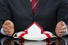 Geschäftsmann-Hand Protecting House-Modell With Lifebelt lizenzfreies stockfoto