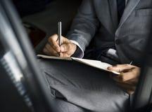 Geschäftsmann Hand Write Note Sit Car lizenzfreie stockbilder