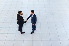 Geschäftsmann-Handerschütterungs-Willkommens-Gesten-lassen Spitzenwinkelsicht, zwei Geschäftsleute Abkommen Händedruck sich anmel Stockfotografie