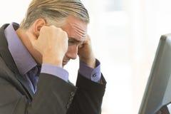 Geschäftsmann-With Head In-Hände im Büro Lizenzfreie Stockbilder