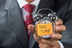 Geschäftsmann Holding Alarm Clock mit Steuer-befristetem Schuldschein Stockfotos