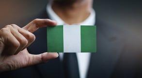 Geschäftsmann-Holding Card Nigeria-Flagge lizenzfreie stockfotografie