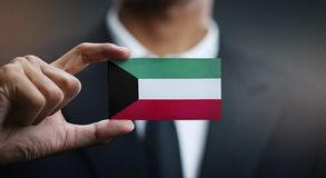 Geschäftsmann Holding Card von Kuwait-Flagge lizenzfreies stockbild