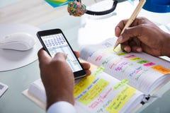 Geschäftsmann-Holding Cellphone Writing-Zeitplan im Tagebuch lizenzfreies stockfoto